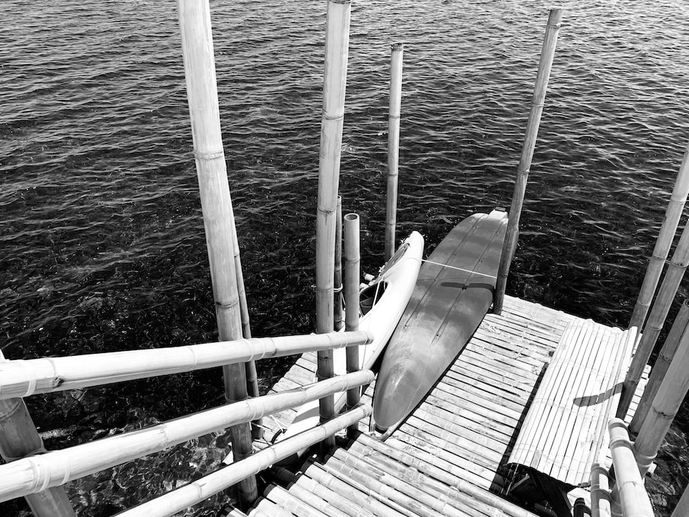 grayscale photo of a boat on a wooden dock