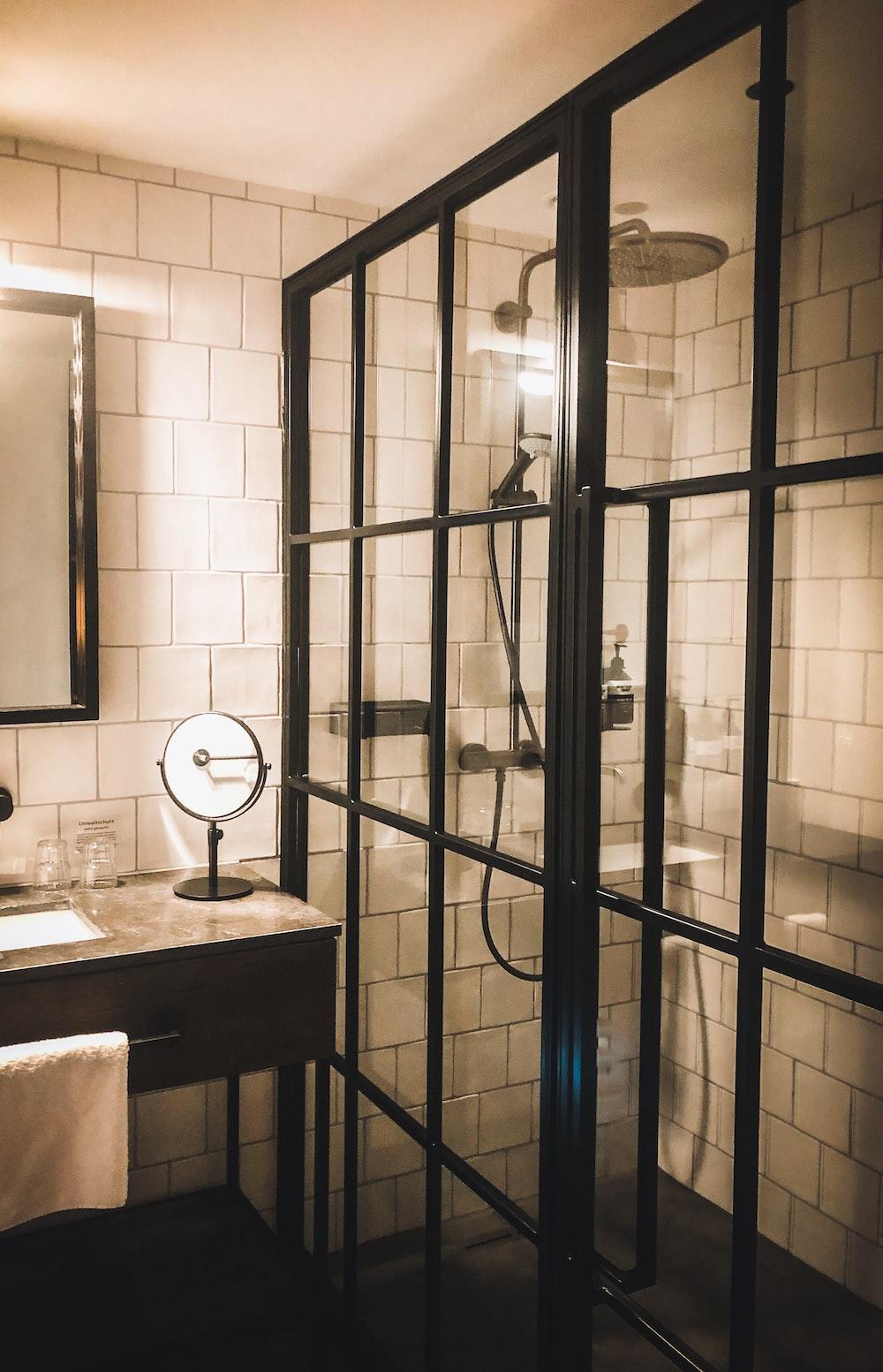 white ceramic sink near black framed glass door
