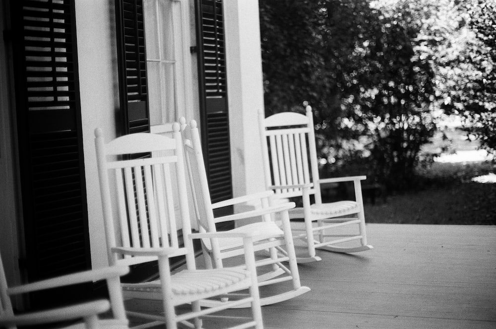 grayscale photo of two rocking chairs