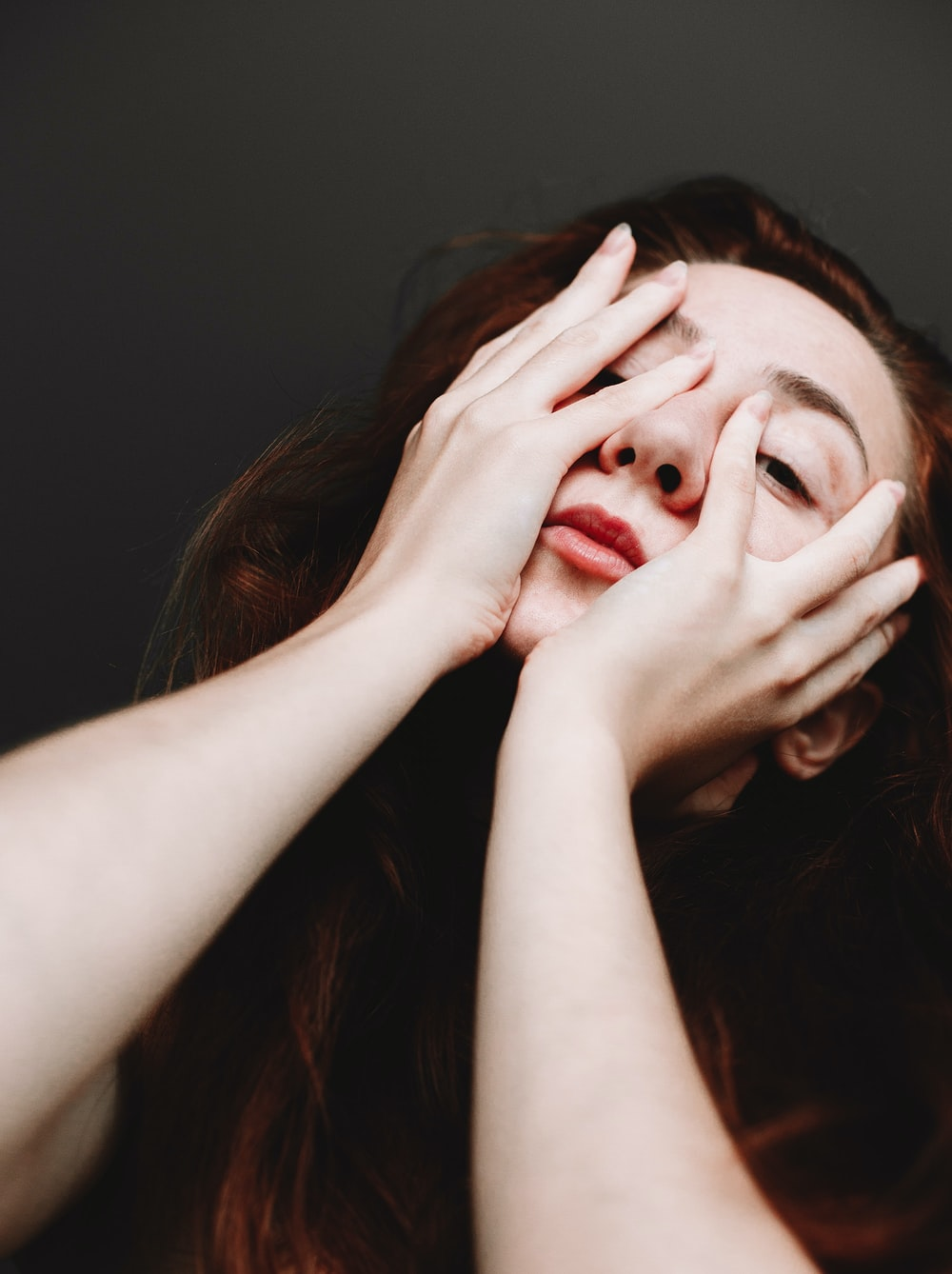 woman covering her face with her hand