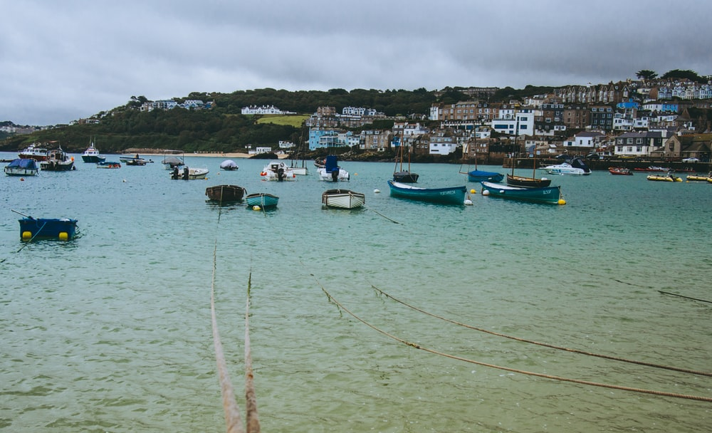 boats on sea under cloudy sky during daytime