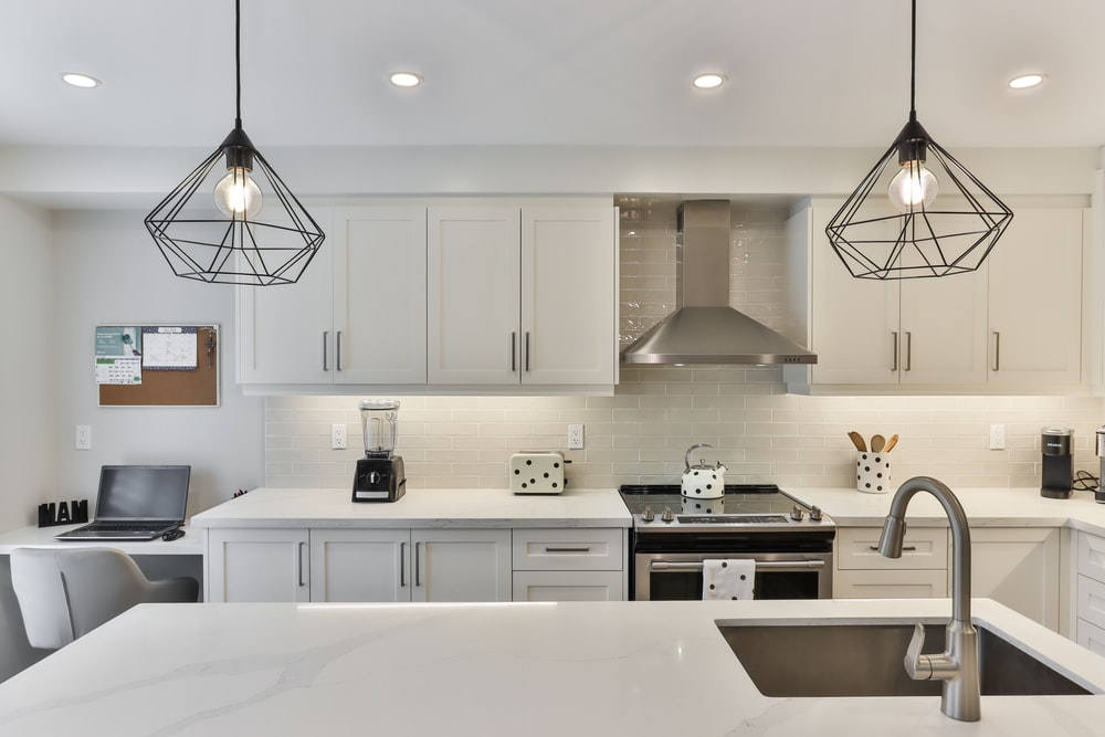 white wooden kitchen cabinet with black pendant lamp