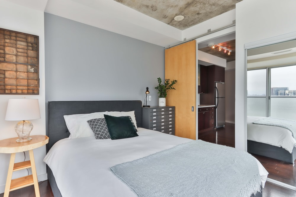 white bed linen near brown wooden door