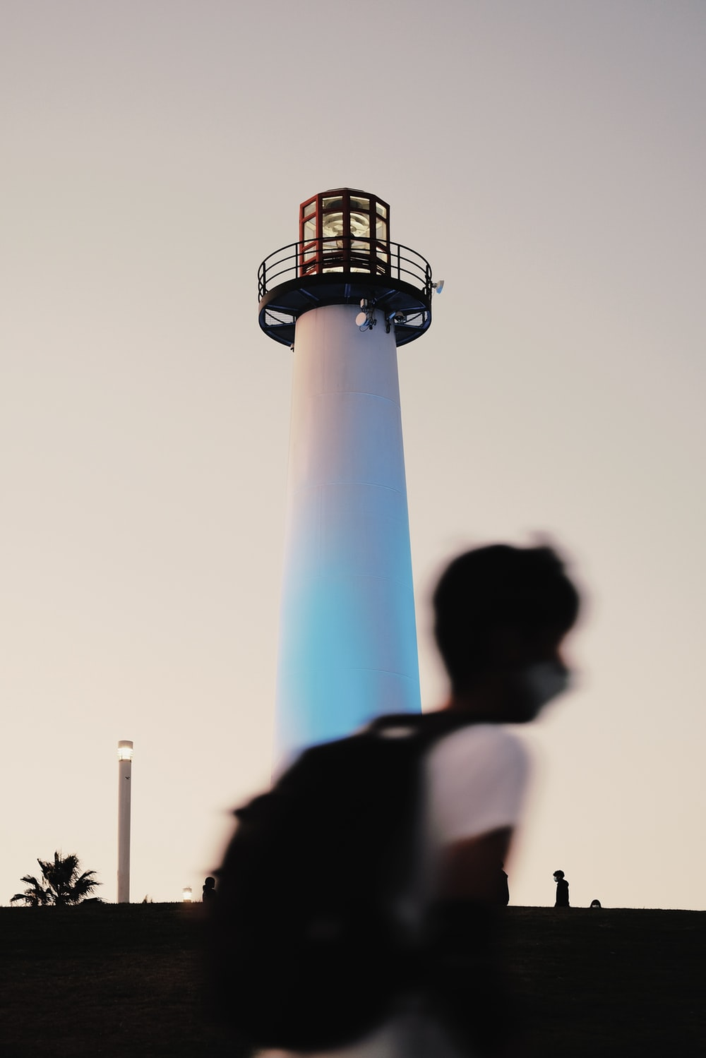 man in white t-shirt standing near white and blue tower during daytime