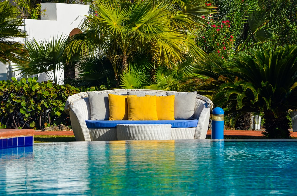 blue and white sofa chair near swimming pool