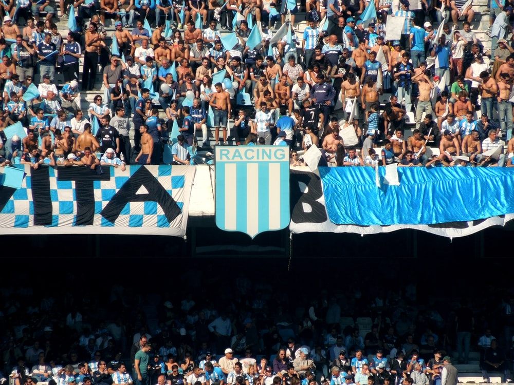 people in a stadium with blue and white curtains
