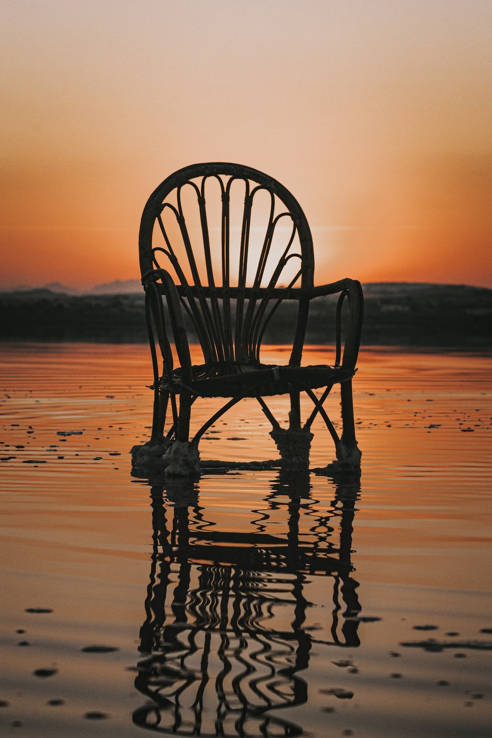 silhouette of wooden chair on beach during sunset