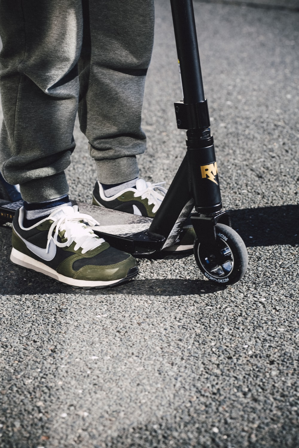 person in blue denim jeans and yellow and black nike sneakers riding black and white bicycle