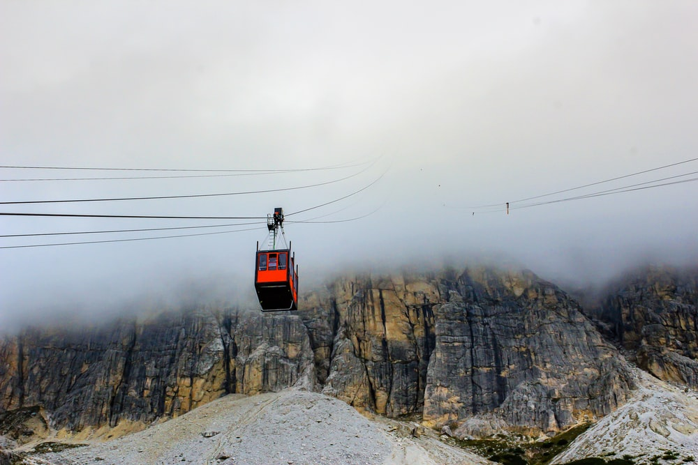 red cable car over snow covered mountain