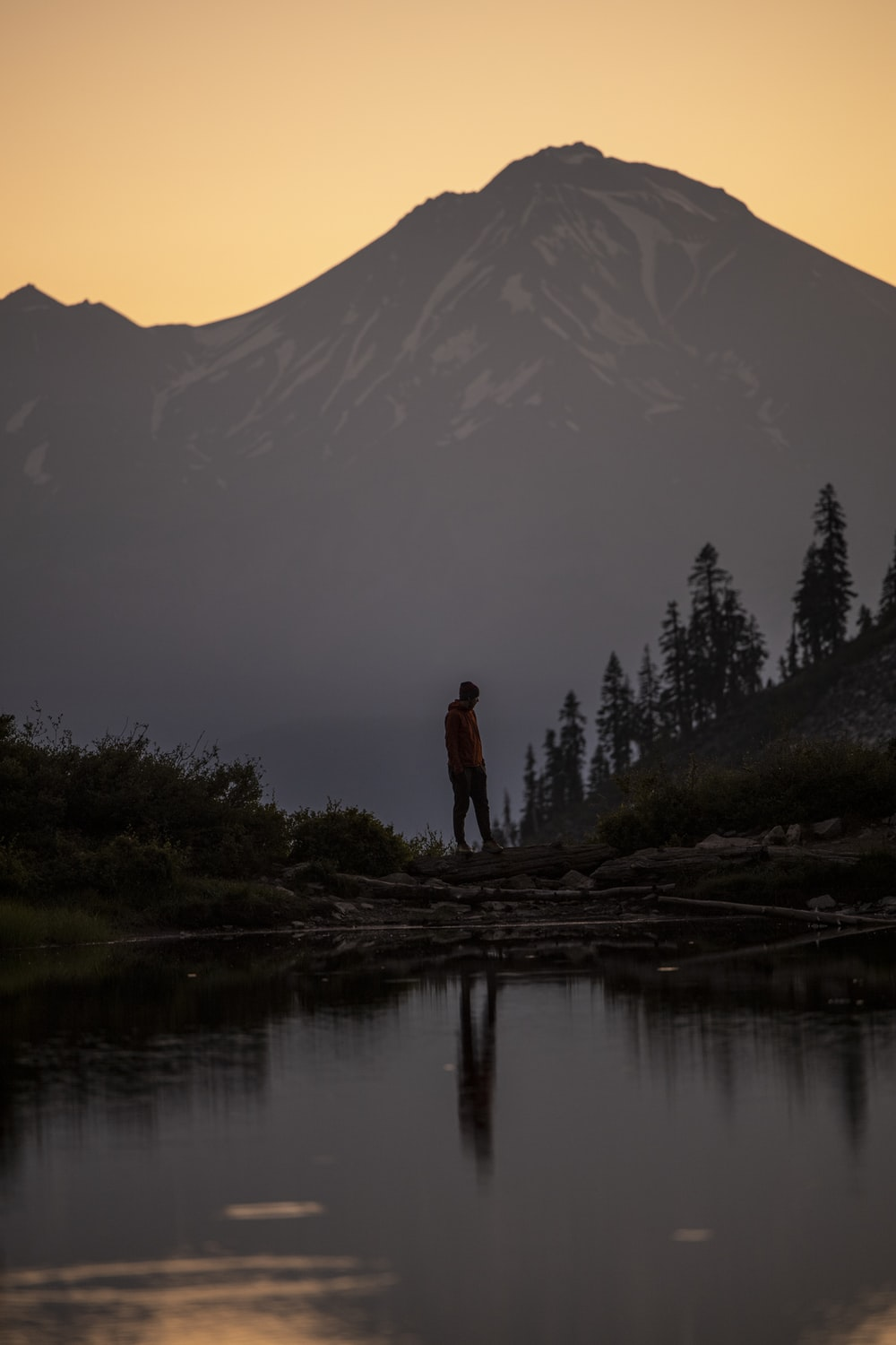silhouette of man standing on rock near lake during daytime