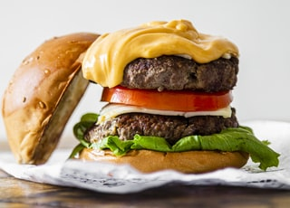 burger with cheese and lettuce on white ceramic plate