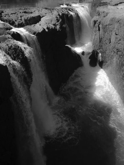 grayscale photo of man in water falls