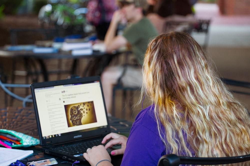 woman in purple shirt using black laptop computer