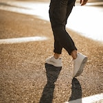 person in black pants and white sneakers walking on brown asphalt road during daytime