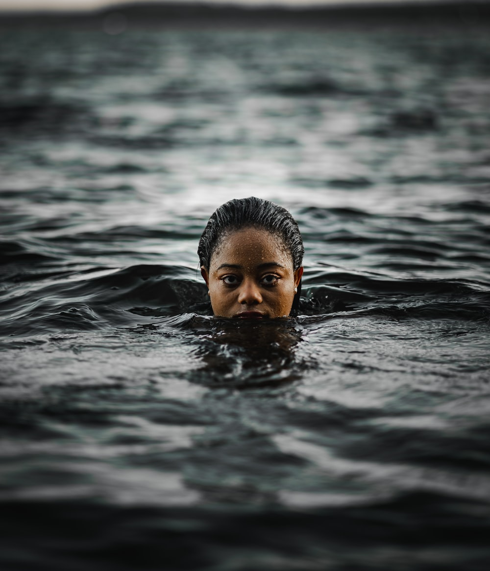 boy swimming in water during daytime