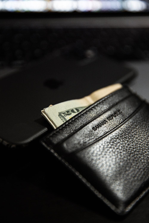 black leather bifold wallet on black laptop computer