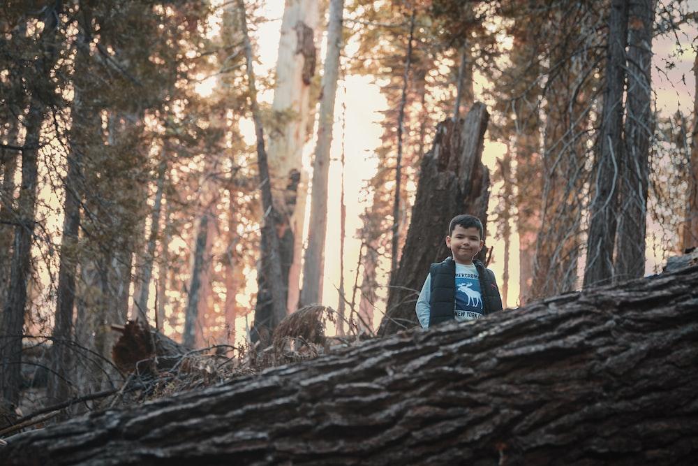 man in blue jacket standing on brown tree log during daytime