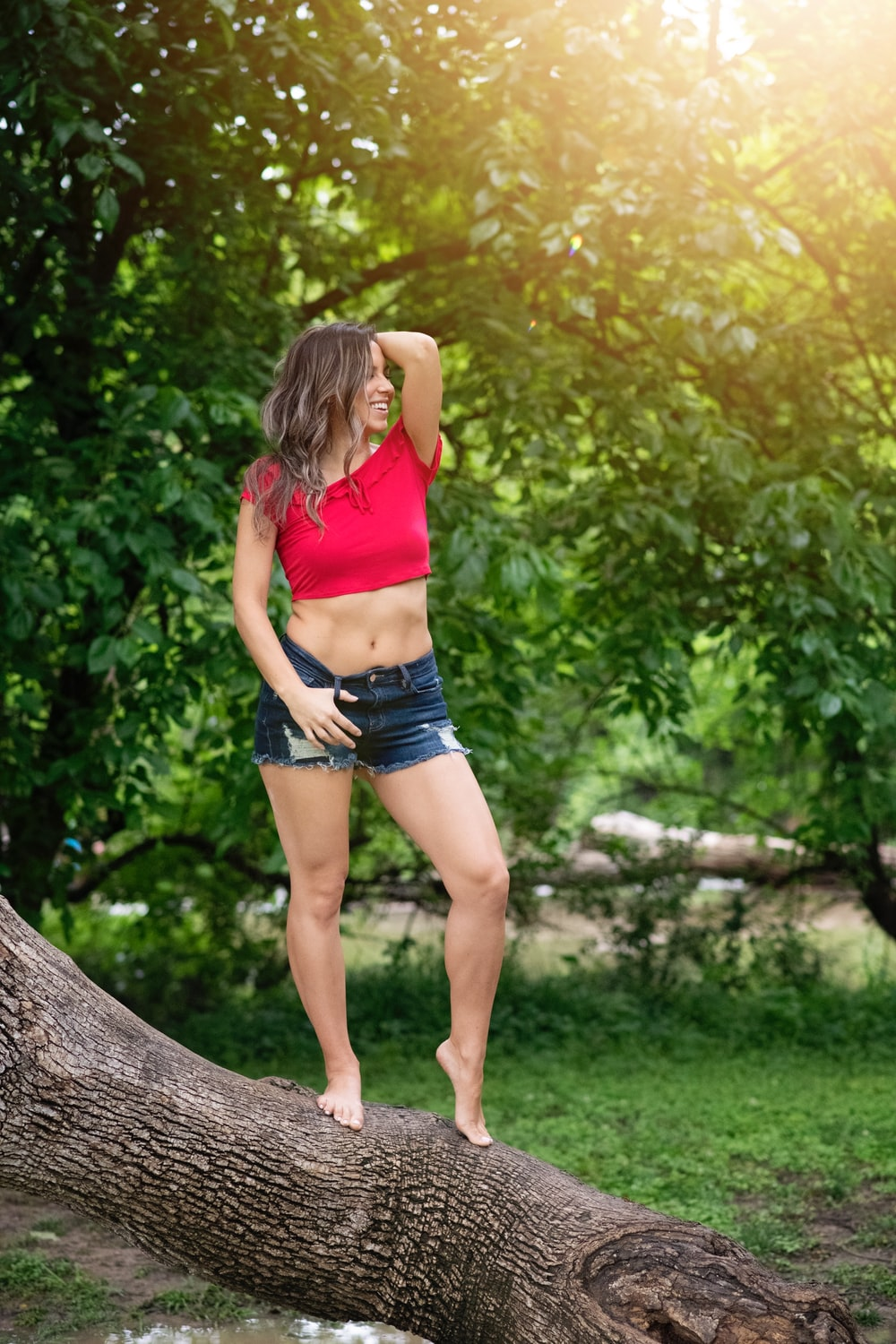 woman in red tank top and black shorts standing on tree trunk during daytime