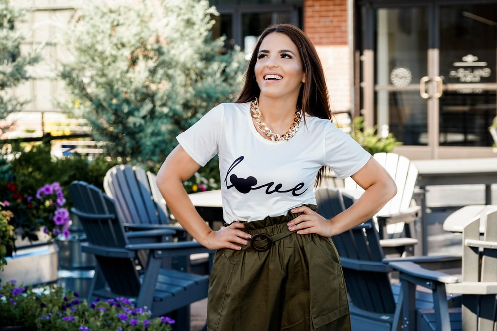 woman in white and black crew neck t-shirt and black skirt standing near brown wooden