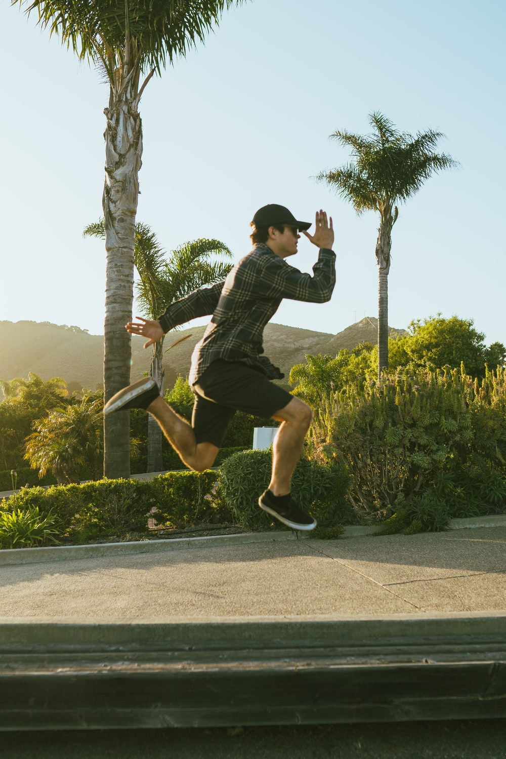 man in black shirt and black shorts jumping on gray concrete road during daytime