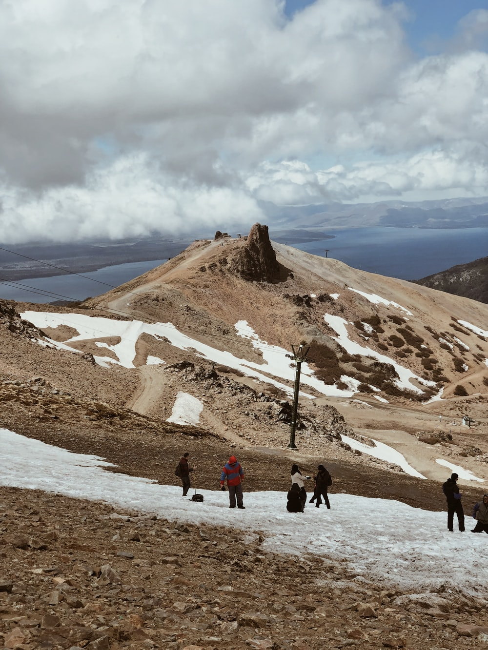 people walking on brown field near brown mountain under white clouds during daytime