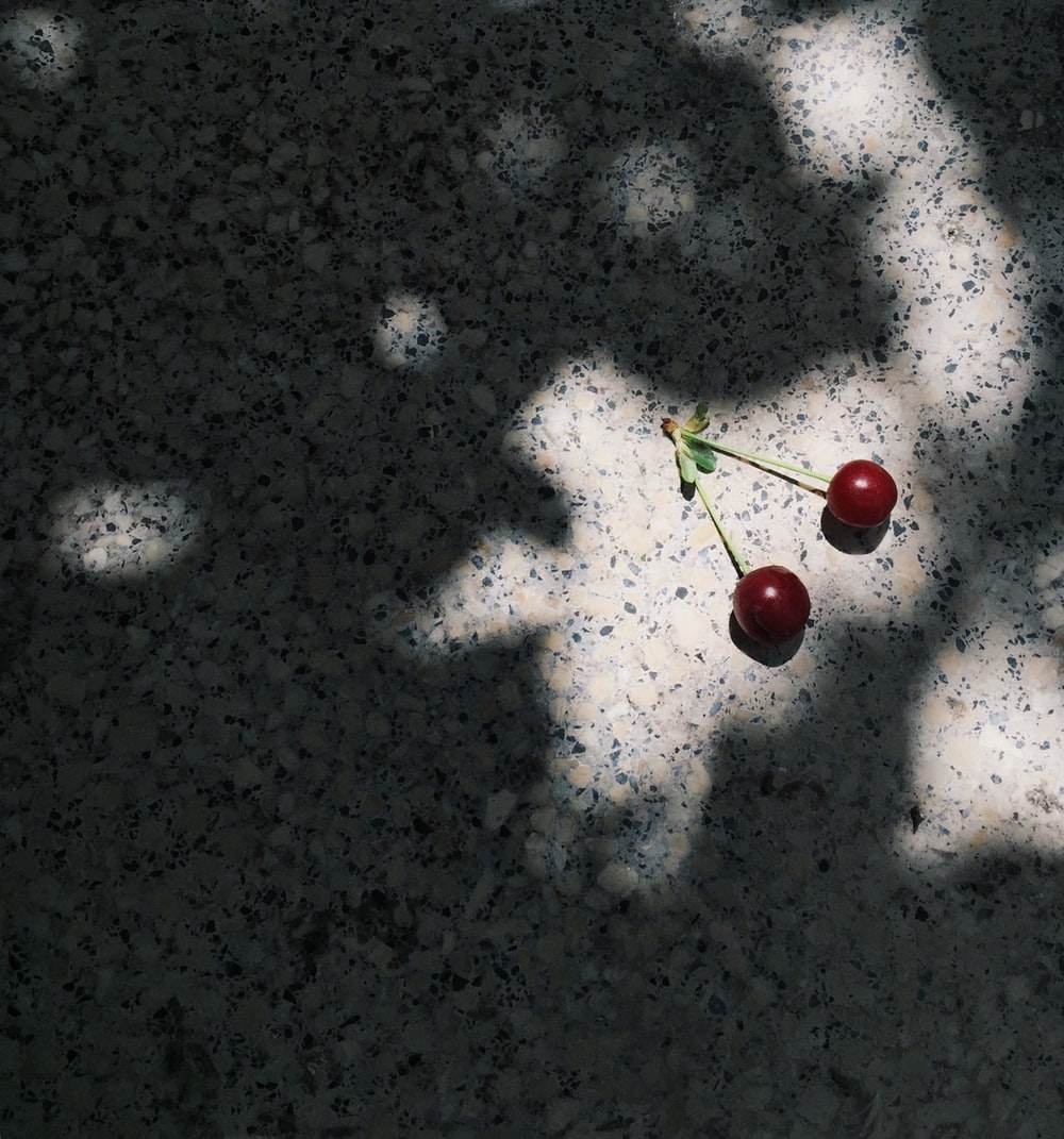 red cherries on white and black marble surface