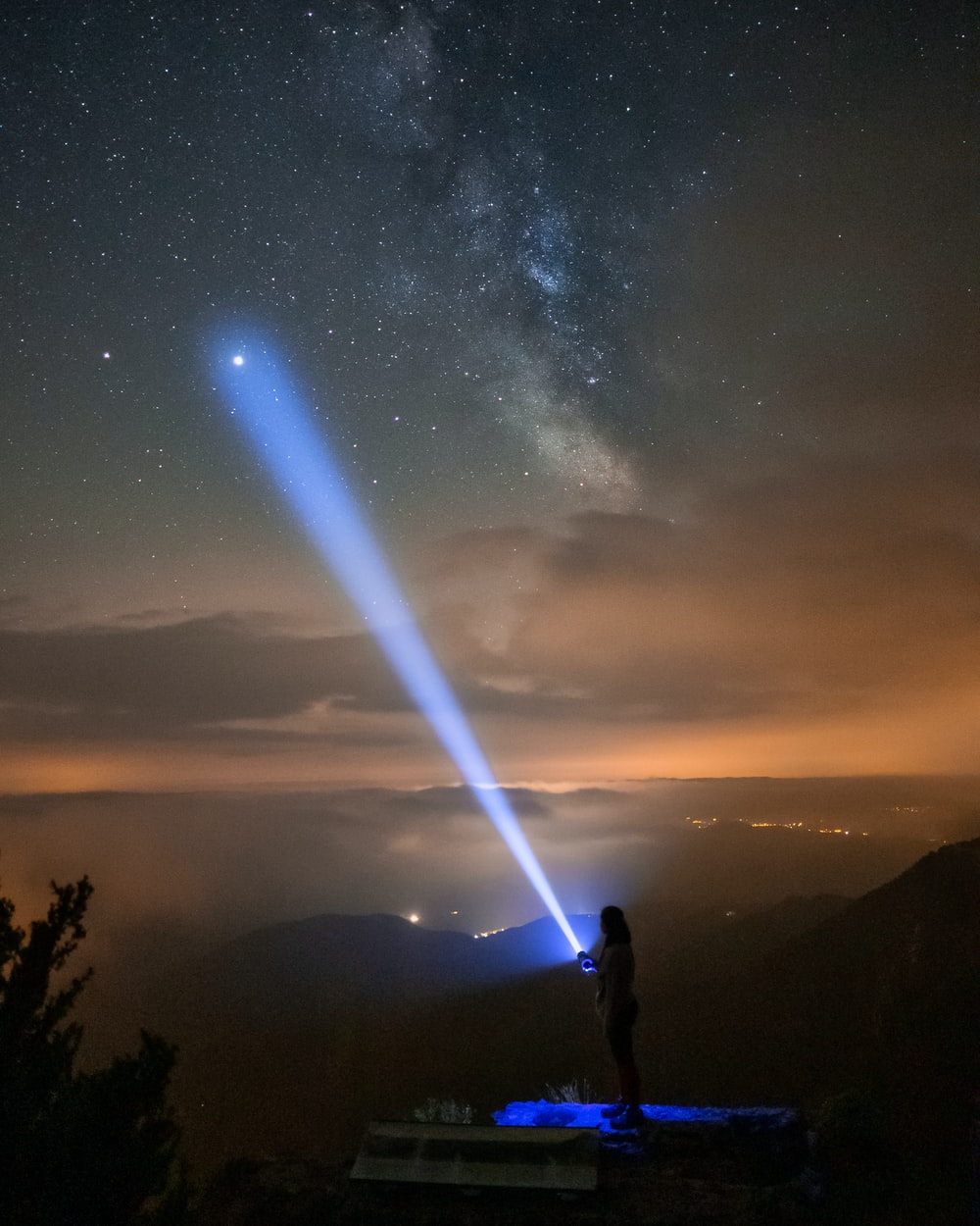 silhouette of man standing on mountain during night time