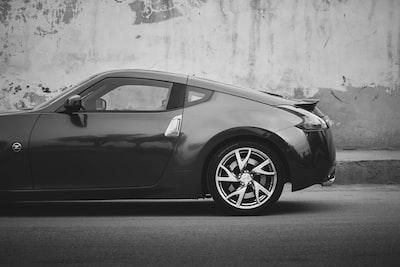 black porsche 911 parked on gray concrete pavement nissan zoom background