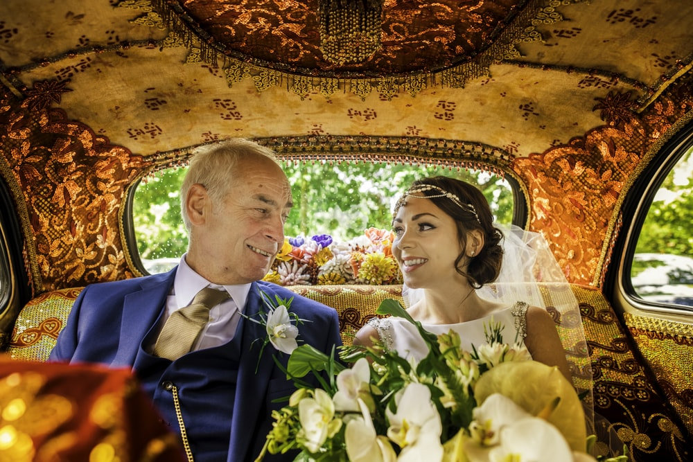 man in blue suit jacket and woman in white wedding dress