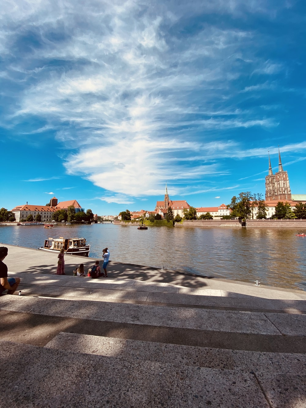 people sitting on concrete bench near body of water during daytime