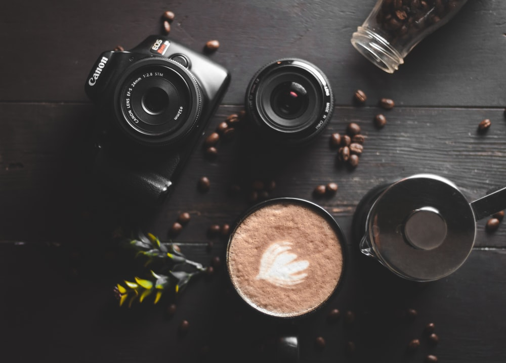 black nikon dslr camera beside brown round round ornament