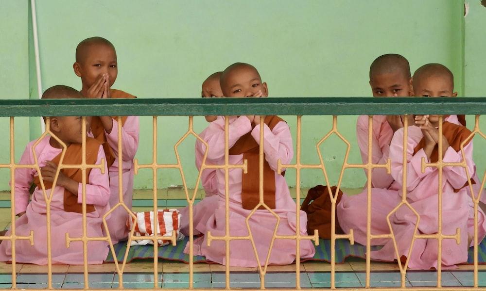 three baby in pink shirt on white metal frame