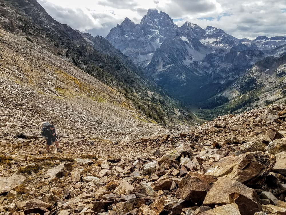 person walking on rocky road near mountains during daytime