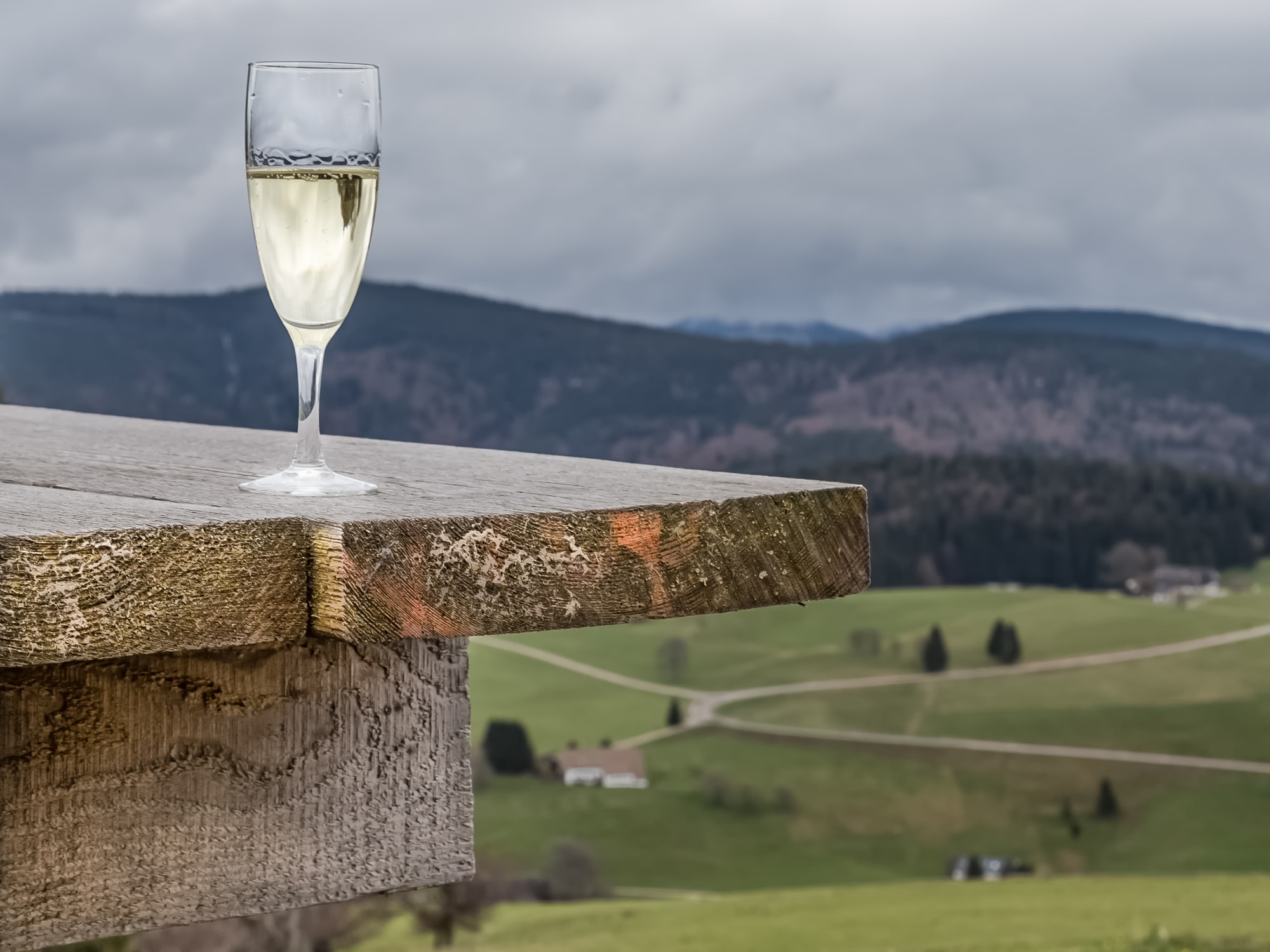 A cold glass of wine stands on a wooden table, outdoors in the European Alps.