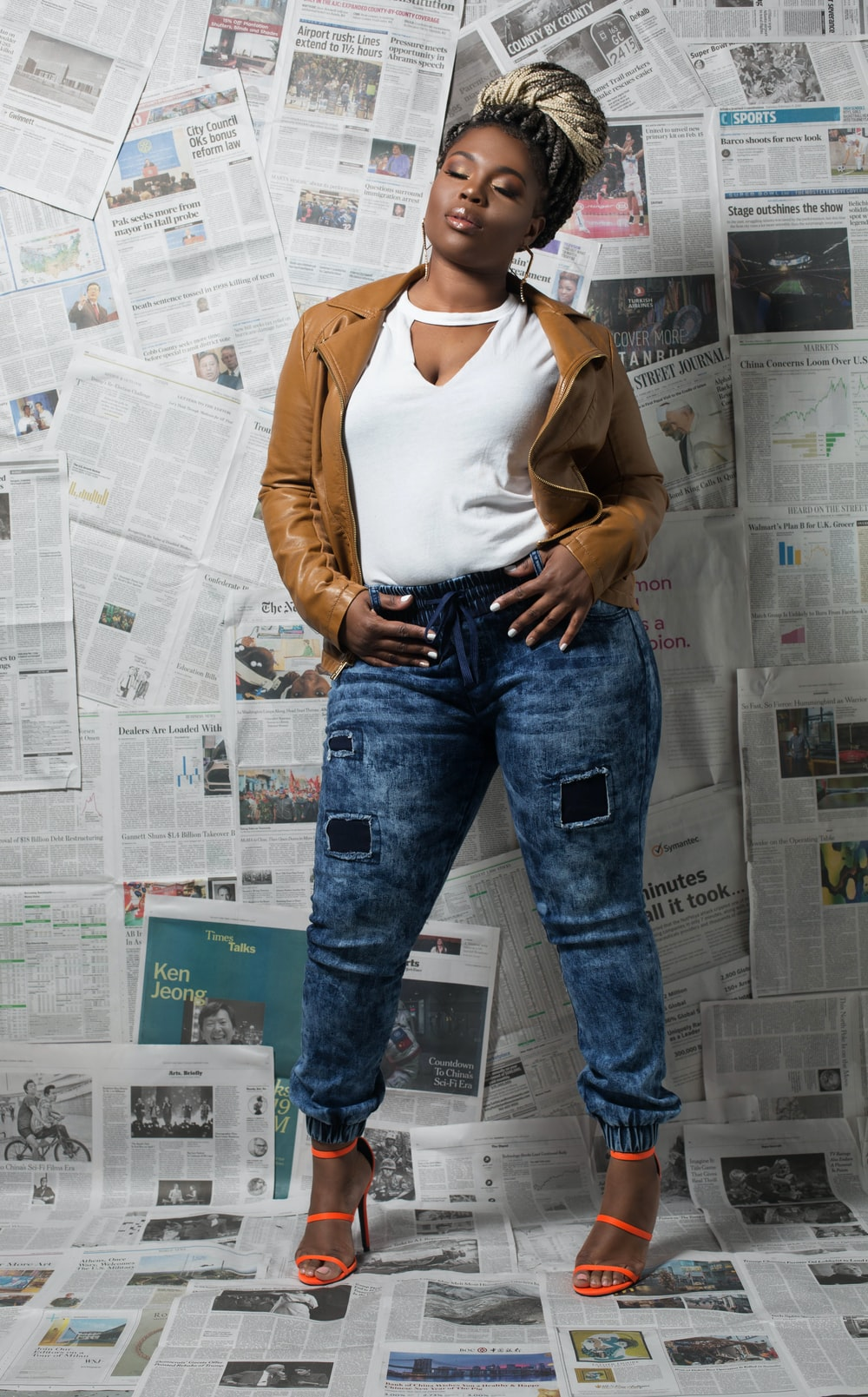 woman in brown cardigan and blue denim jeans standing beside white wall