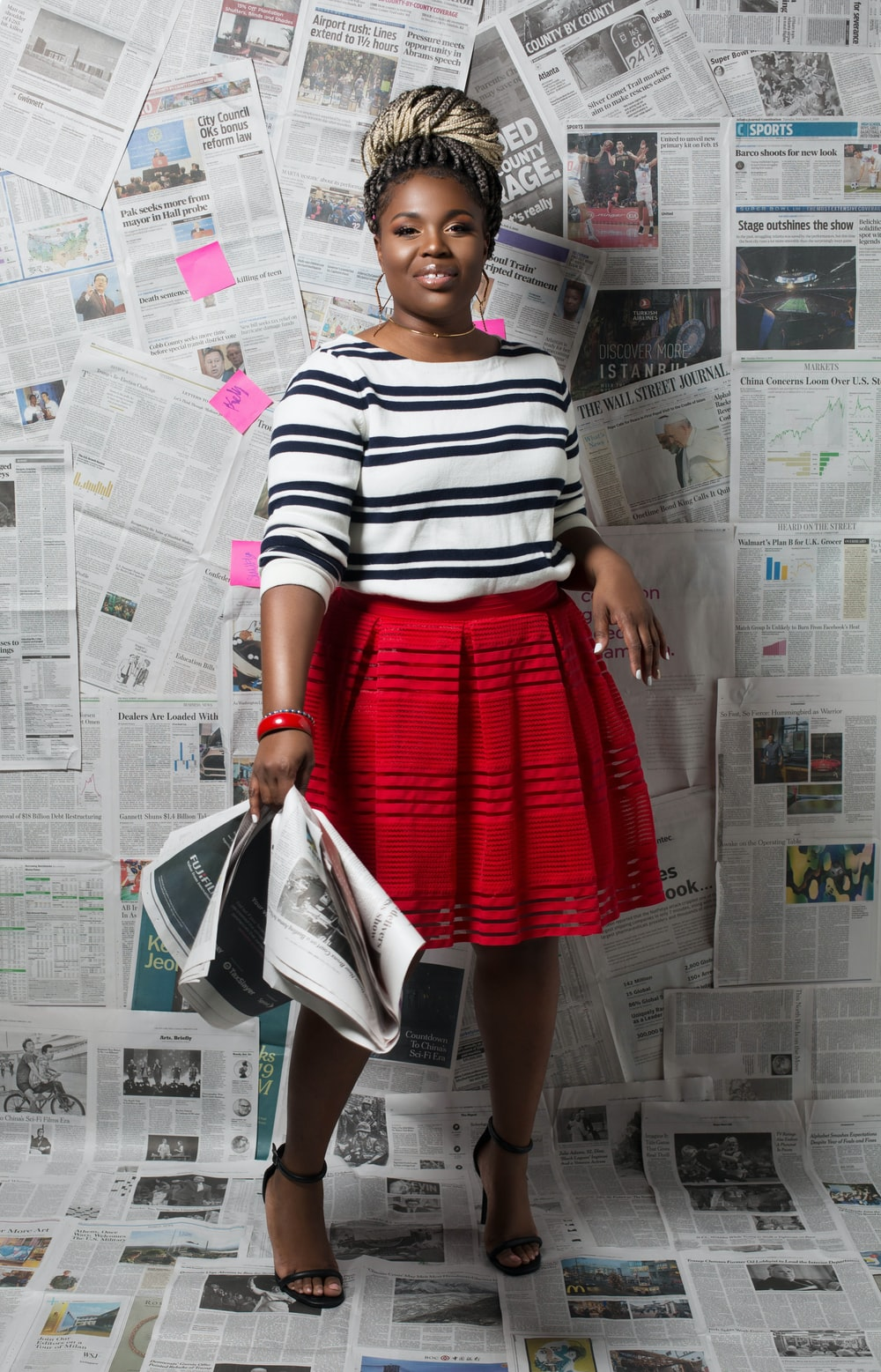 woman in white and black stripe shirt and red skirt standing