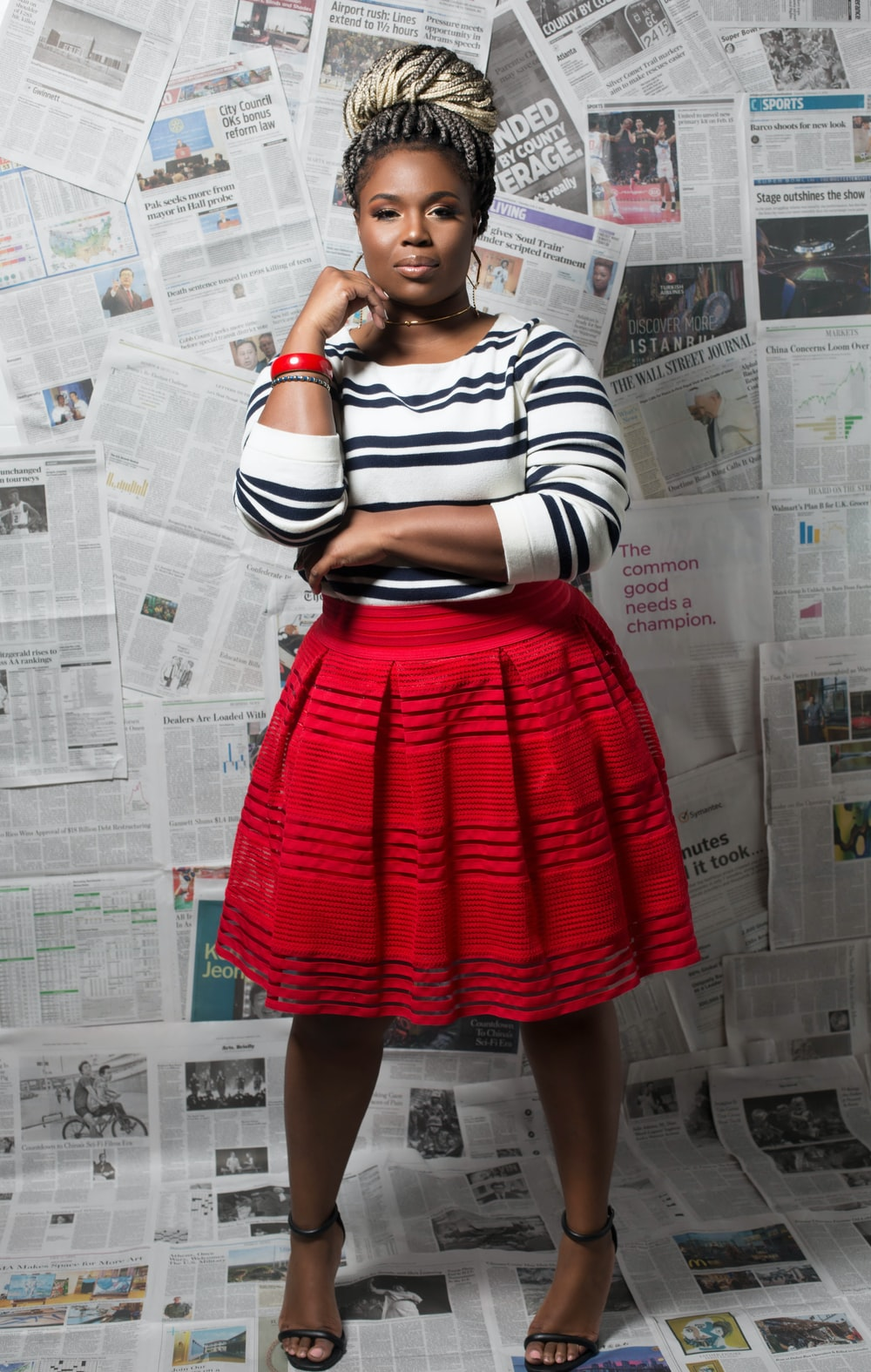 woman in black and white striped long sleeve shirt and red skirt standing beside white wall