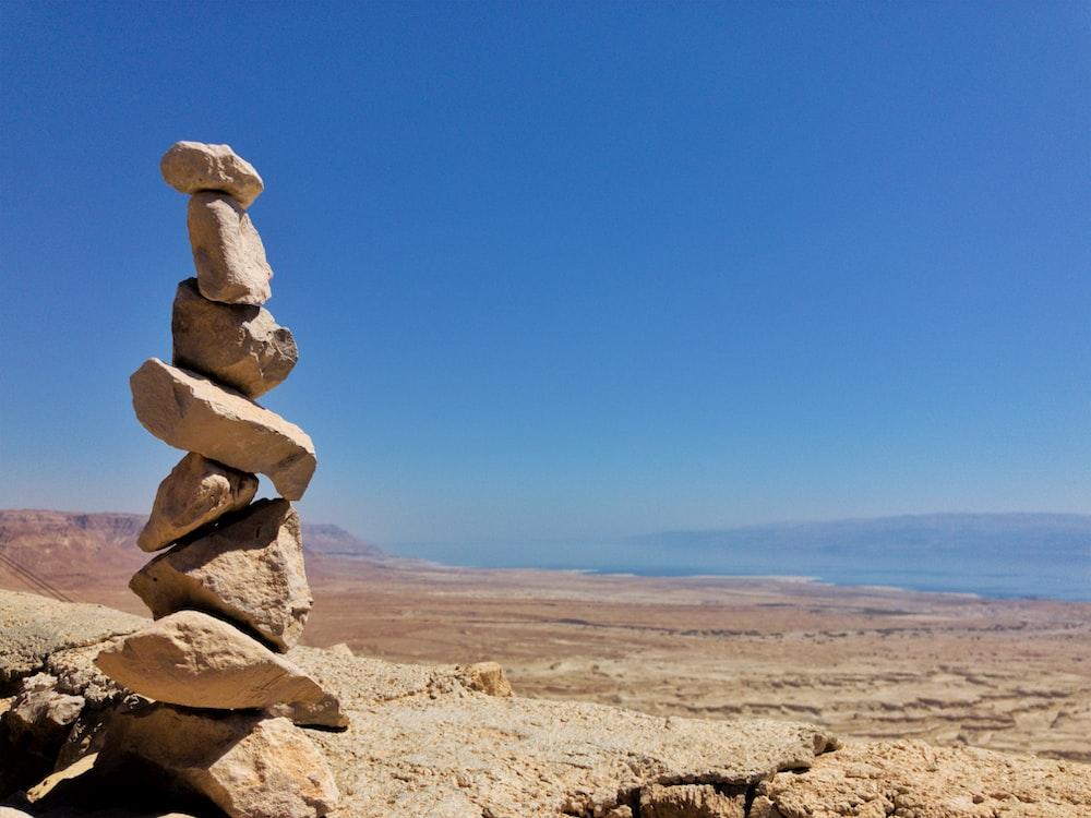brown rocks on brown sand under blue sky during daytime