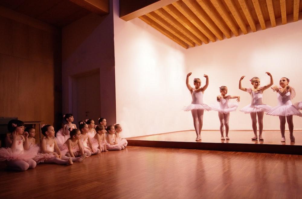 group of people dancing on brown wooden floor