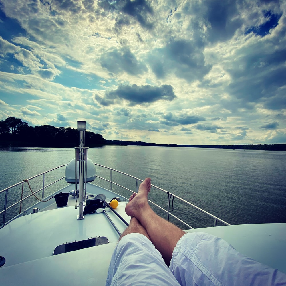 person in white pants sitting on boat during daytime