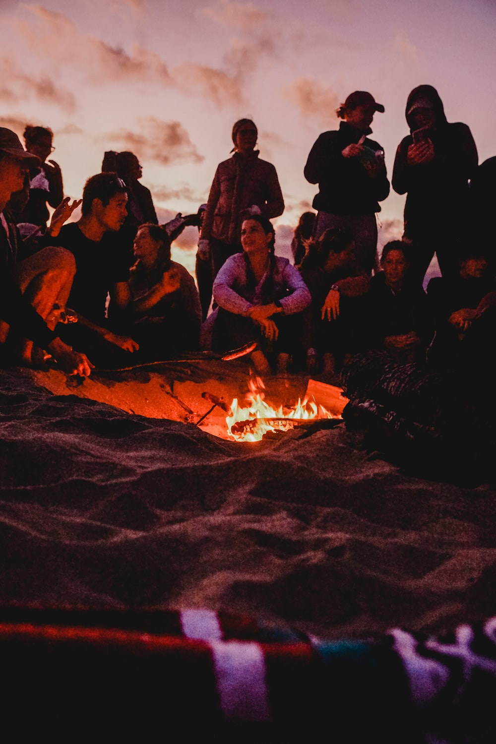 people sitting on brown sand near bonfire during night time