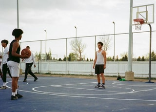 group of people playing basketball during daytime