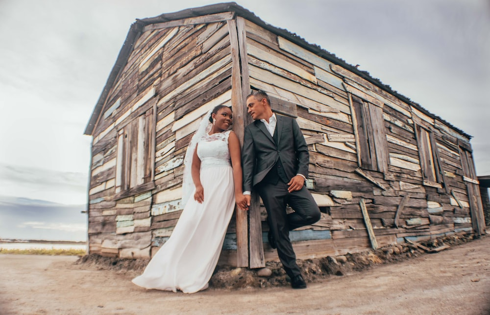 man and woman in wedding dress standing beside brown wooden house during daytime