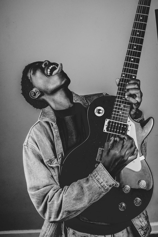 man in denim jacket playing electric guitar