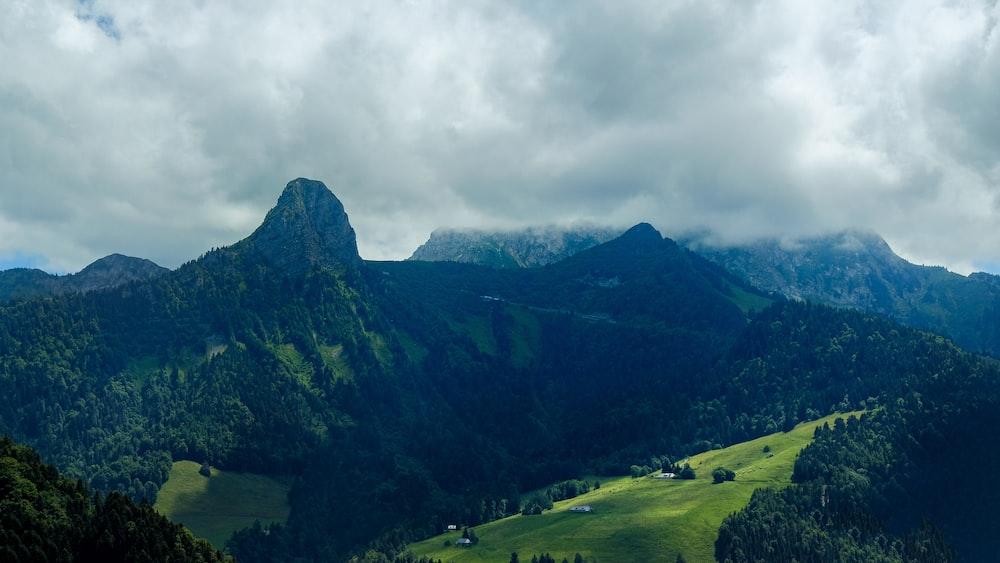 green grass field near mountain under cloudy sky during daytime
