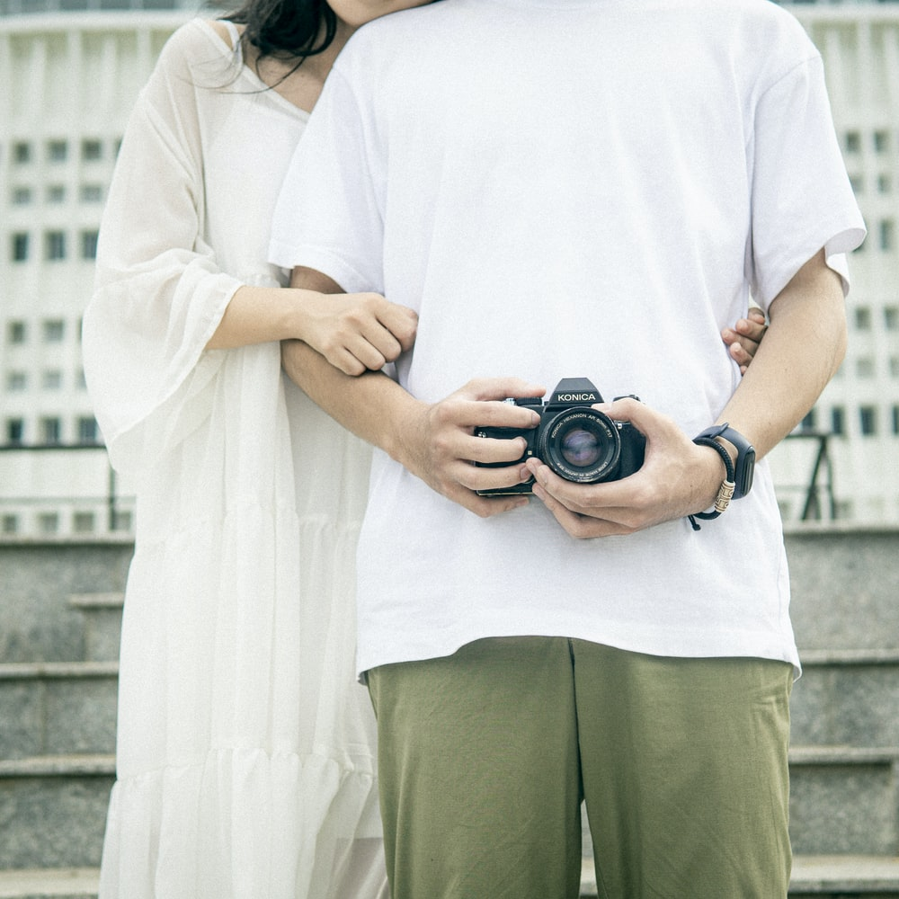 woman in white t-shirt and green pants holding black dslr camera