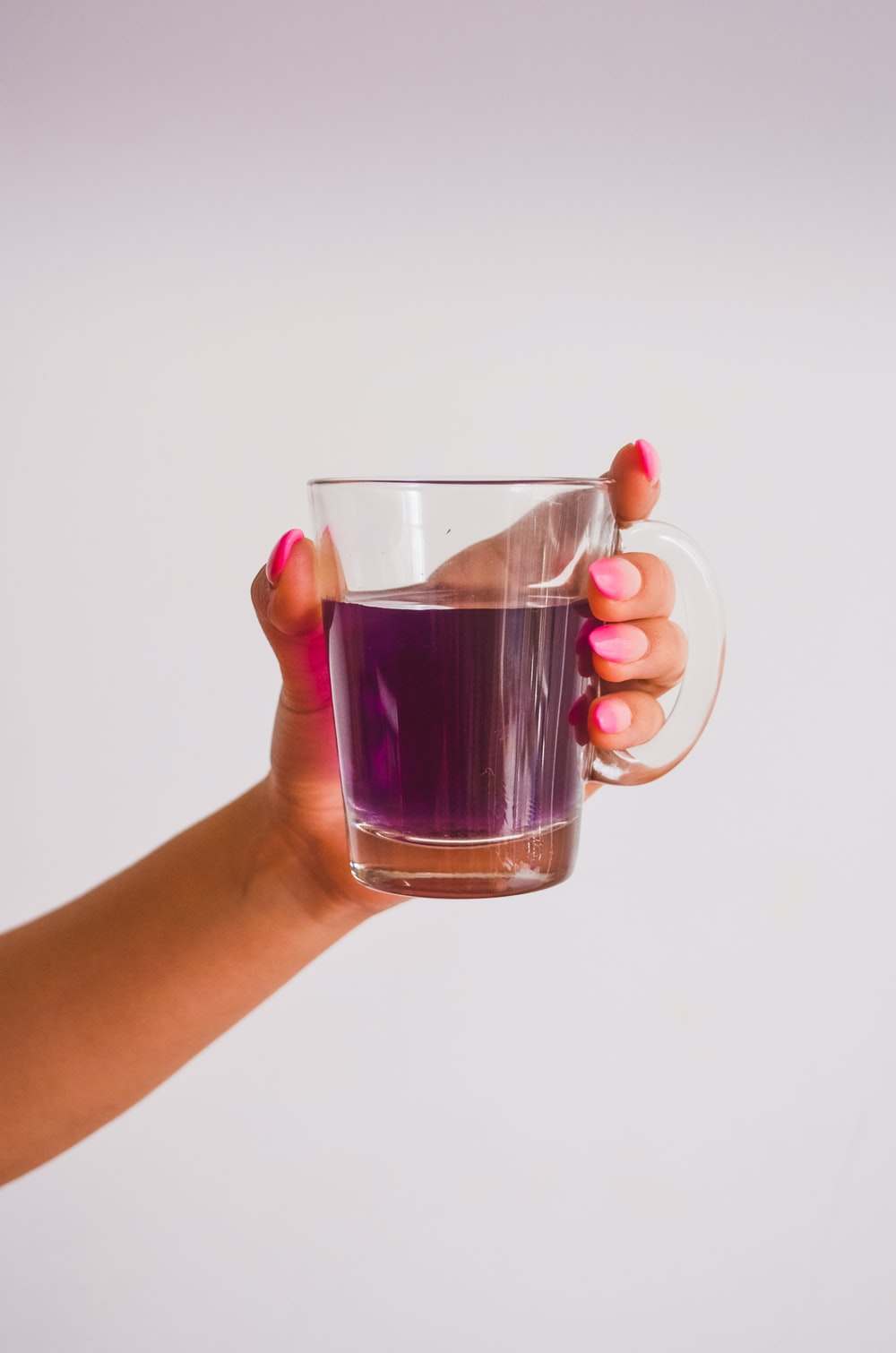 person holding clear glass mug with brown liquid