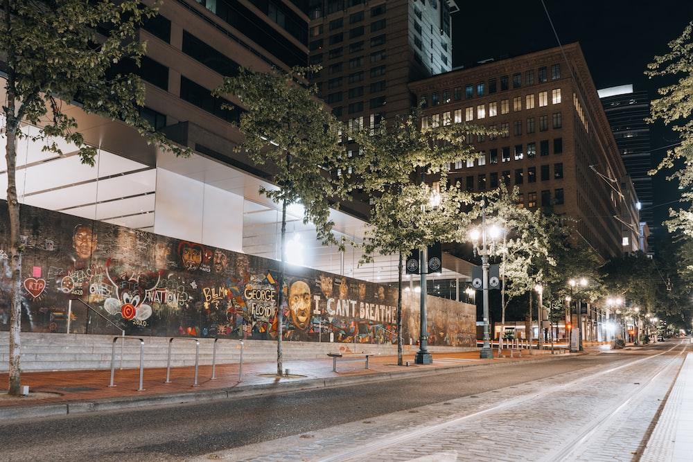 people walking on sidewalk near building during nighttime