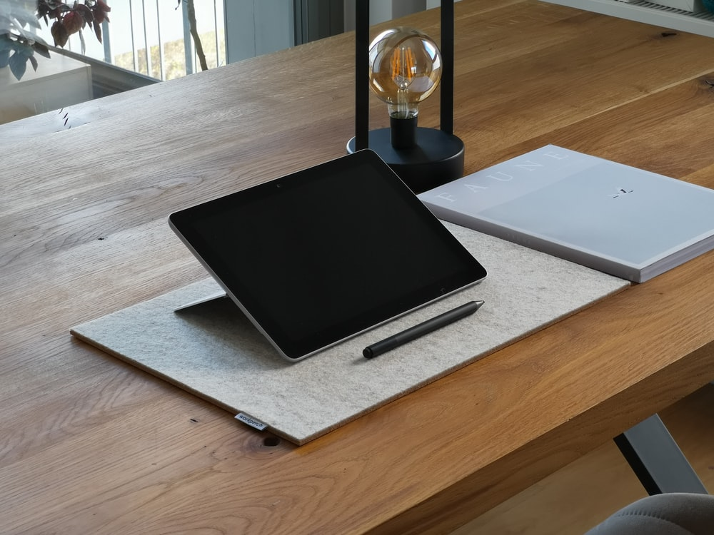 black ipad on brown wooden table
