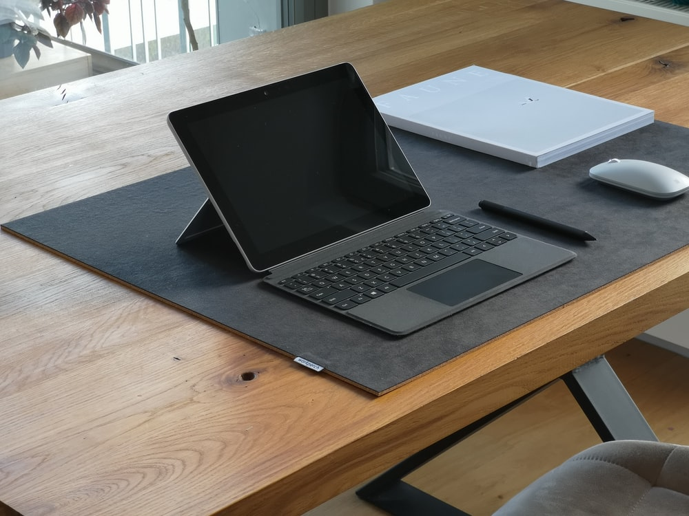 black and silver laptop computer on brown wooden table